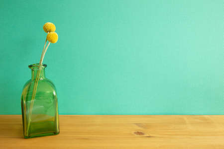 Vase of yellow Craspedia dry flowers on wooden table. mint green wall background