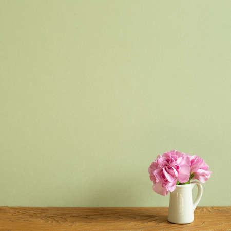 Vase of pink carnation flowers on wooden table. khaki green background