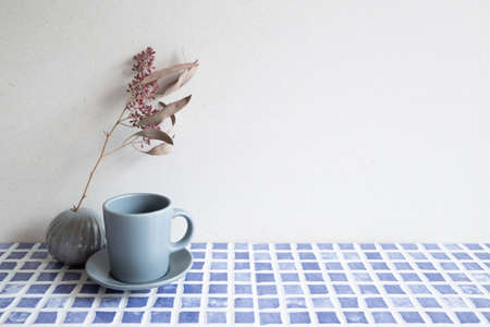 Gray coffee cup and vase of dry flowers on blue ceramic mosaic tile table. white wall background. home interior