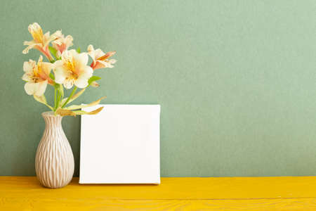 Blank white canvas and vase of Yellow Alstroemeria flowers on wooden table. green background 免版税图像
