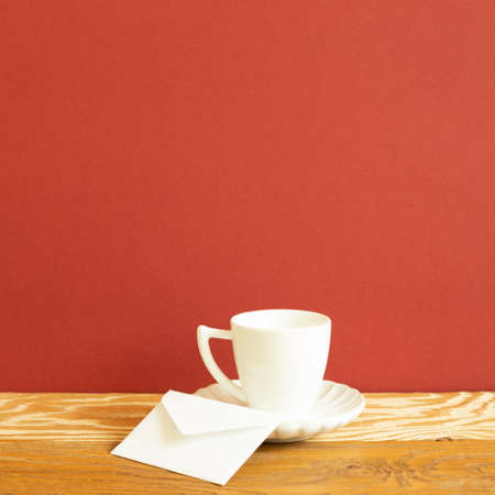 White coffee cup and envelope on wooden table. red background