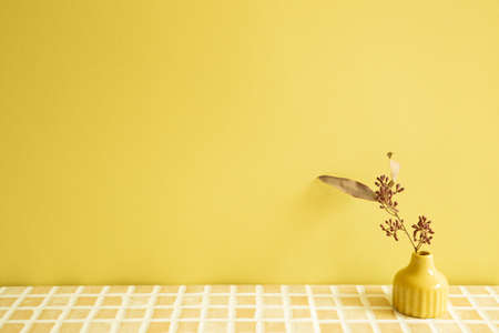 Vase of dry flowers on beige ceramic mosaic tile table. yellow wall background. home interior
