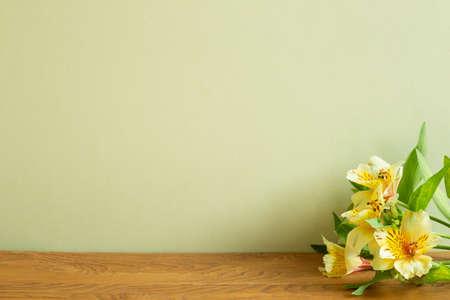 Yellow alstroemeria flowers on wooden table. khaki green background