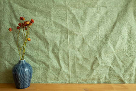 Vase of orange dry flowers on wooden table. green fabric background. home interior