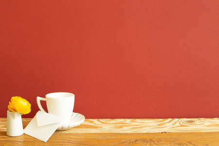 White coffee cup and envelope with yellow ranunculus flower on wooden table. red background 免版税图像