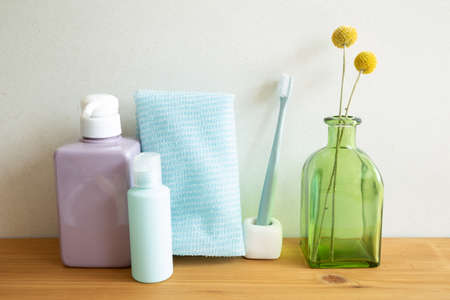 Bathroom bottles, shower towel, toothbrush, vase of plant on wooden table. white wall background. Skin care and spa concept