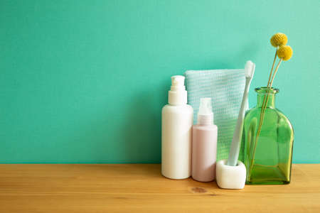 Bathroom bottles, shower towel, toothbrush, vase of plant on wooden table. mint wall background. Skin care and spa concept