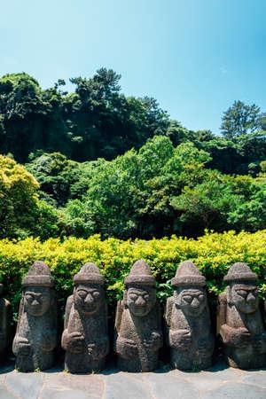 Dol hareubang stone grandpa sculpture at Cheonjiyeon Falls in Jeju Island, Korea Reklamní fotografie