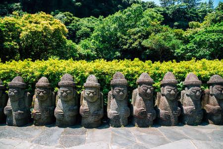 Dol hareubang stone grandpa sculpture at Cheonjiyeon Falls in Jeju Island, Korea