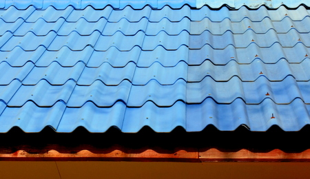 damaged roof: Blue roof  tiles replace the damaged parts Stock Photo