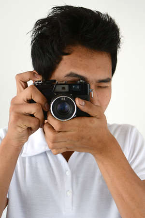 finder: Young man taking photograph with range finder film camera