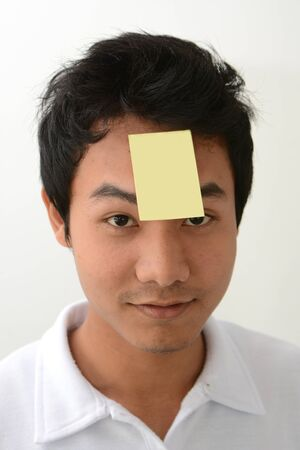 small paper: Young man with small paper attach to his forehead