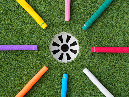 Colorful golf grips point to the hole with ball inside
