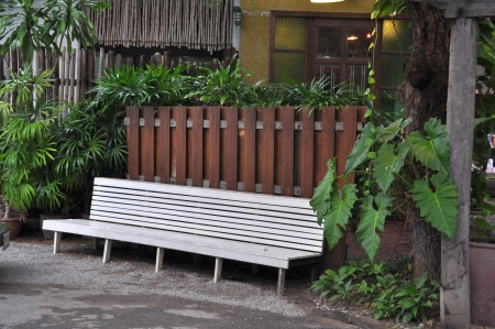 White bench with wood fence and green bush in background photo