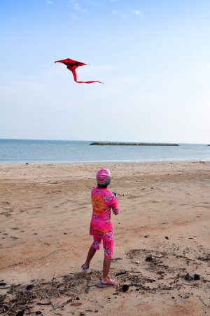Rear view of young girl on sand beach with colorful kite , sea and cloudscape in background. photo