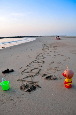 Alphabet letters handwritten in sand on beach with green bucket and a doll