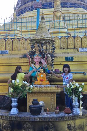 daw: Yangon,Myanmar - 28 November 2015: Unknown tourists pour water to buddha statue at temple of Shwe Maw Daw Pagoda in Yangon,Myanmar.Part of the old pagoda was destroyed by an earthquake in 1917.