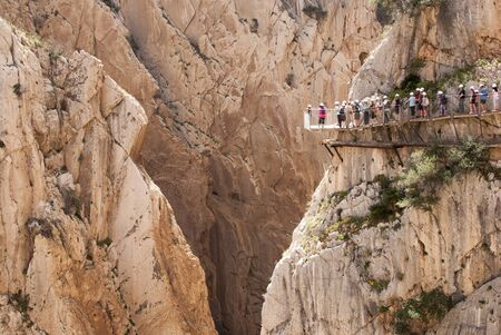 Wooden walkway with a row of people in a rocky cut of the Caminito del Rey on the Gudalhorce River in the Desfiladero de los Gaitanes Natural Area