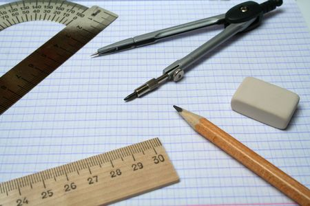 Compasses, pencil, eraser and rulers on squared paper photo