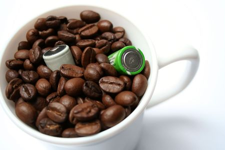Two batteries in a cup with grains of coffee