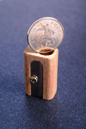 The Russian coin on a sharpener for pencils made of wood on a color paper photo
