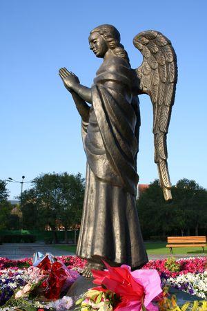 angel de la guarda: Escultura de bronce de un �ngel orando sobre un fondo de flores, (buscar im�genes similares en mi cartera)