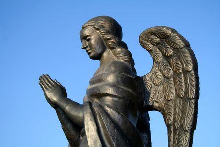 christian angel: Fragmento de una escultura de bronce de un �ngel rezando sobre un fondo de cielo una vista lateral, aislada (buscar im�genes similares en mi cartera)  Foto de archivo
