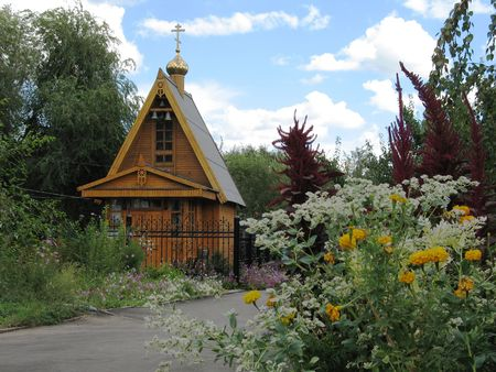Orthodox wooden chapel with a campanile and the gilt dome in the center of city park, (look similar images in my portfolio) Stock Photo