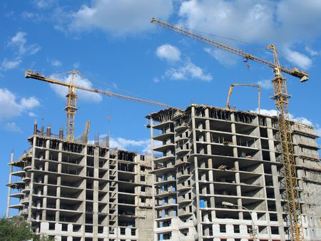 Two elevating cranes of yellow color on a construction site in Volgograd, (look similar images in my portfolio)