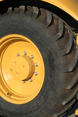 Wheel of a new yellow building tractor close, (look similar images in my portfolio) Stock Photo