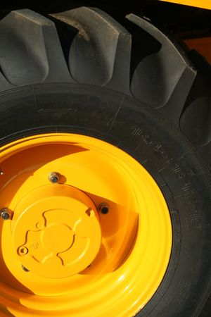 New wheel of a yellow building tractor with bracing, (look similar images in my portfolio) Stock Photo