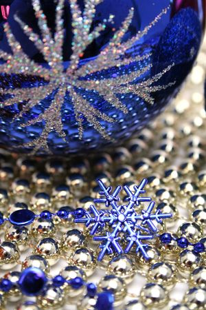 Glass celebratory sphere and snowflake of dark blue color on a background from a beads  photo