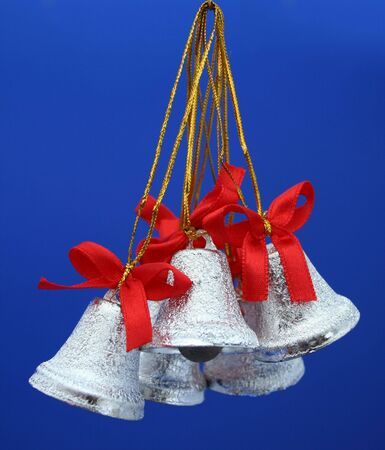 Christmas celebratory handbells of silvery color on a dark blue background