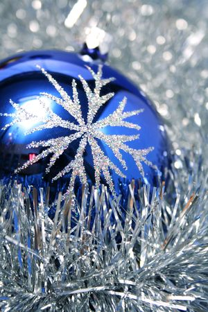 New Years glass sphere of dark blue color with a pattern on a background of a christmas tinsel Stock Photo