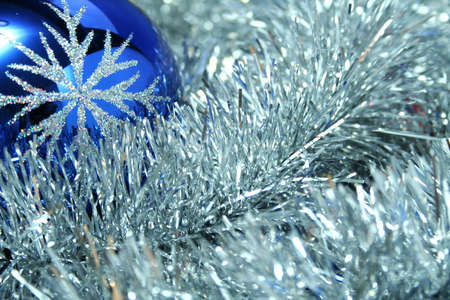 Celebratory glass sphere of dark blue color with a pattern on a background of a silvery New Years tinsel photo