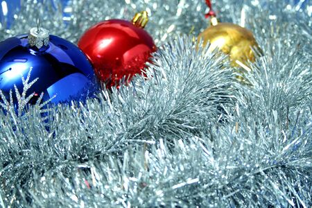 Three celebratory sparkling spheres of dark blue, yellow and red color on a background of a silvery New Year's tinsel Foto de archivo