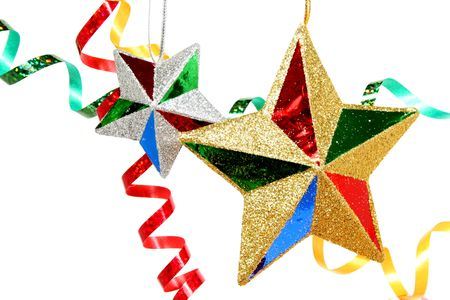 Multi-coloured celebratory streamer and two christmas stars on a white background  Stock Photo