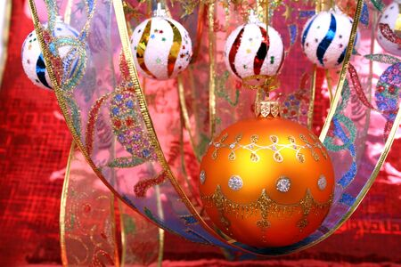 Orange christmas sphere with a pattern and celebratory ribbon on a red background