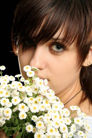 The young beautiful girl with flowers, isolated on a black background