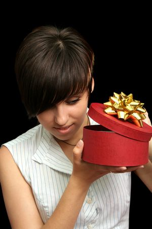 youngs: The young girl looks in a box with a gift, isolated on black background