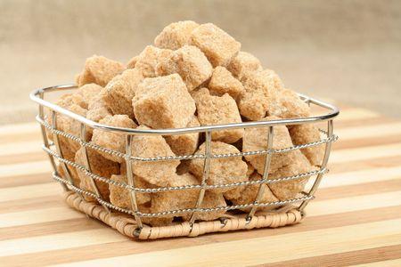 Heap of not refined brown reed sugar in a steel basket
