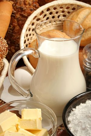 Jug of milk, butter and flour, background photo