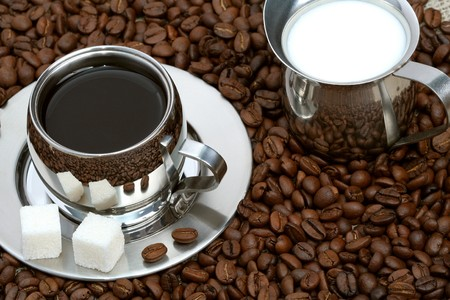 Cup of coffee with lump sugar, milk and coffeebeans, coffee series