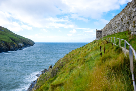Beautiful coastline with green grass and great wall of Peel Castle in Peel, Isle of Man.