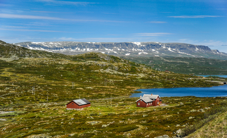 Beautiful landscape and scenery of Norway, the hills and mountain covered partially with white snow and blue lake