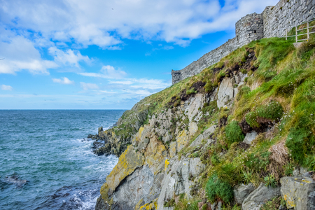 Isle of Man seashore landscape covered with green grass and great wall of Peel Castle in Peel city, Isle of Man