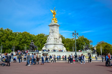 Tourist visiting Victoria Memorial in front of  Buckingham Palace, also known as Buckingham House, located in the city of Westminster, United Kingdom Editorial