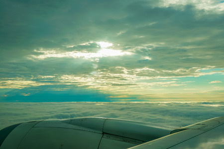 Beautiful view of clouds and sky with sunlight in the morning looking through an airplane window