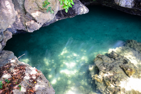 Shallow sea water surface shines through the bottom of the sea surrounded with stone and rock