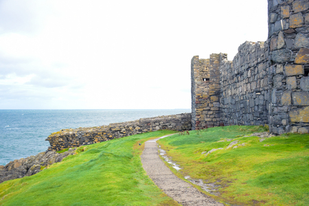 Walk path through the green grass around the great wall of Peel Castle up on St Patrick's Isle in city of Peel, Isle of Man